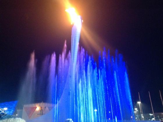 в свете огня и водяной пыли фонтана
